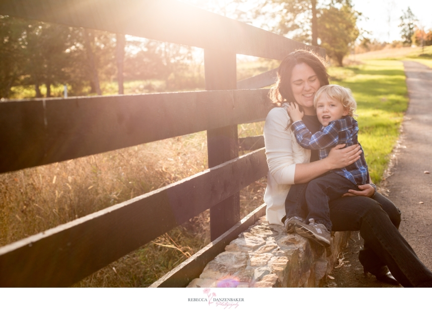Photo of mom and son beside a fence in Willowsford with sun flare