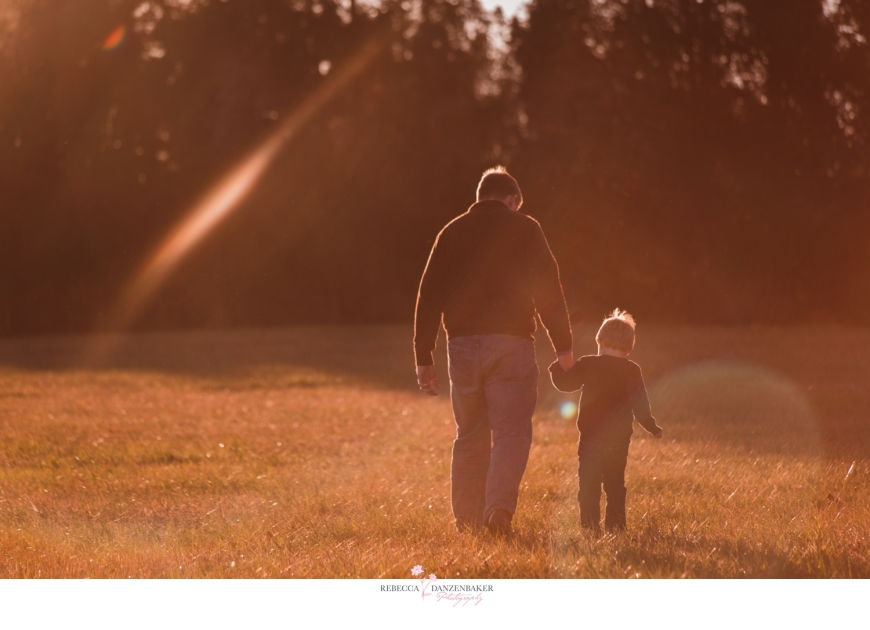 father and son walking in field with sun flare