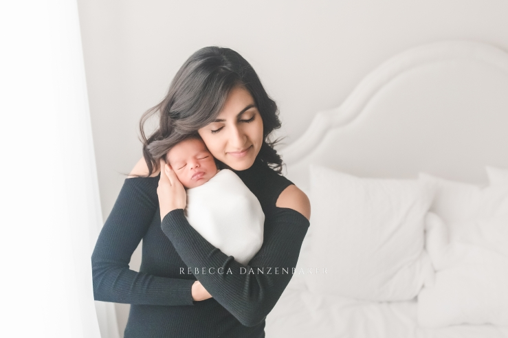 Portrait of a mother and her newborn son in a Northern Virginia all-white photography studio bedroom.