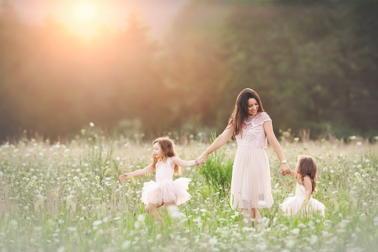 mother and two daughters walking in wildflowers family portrait